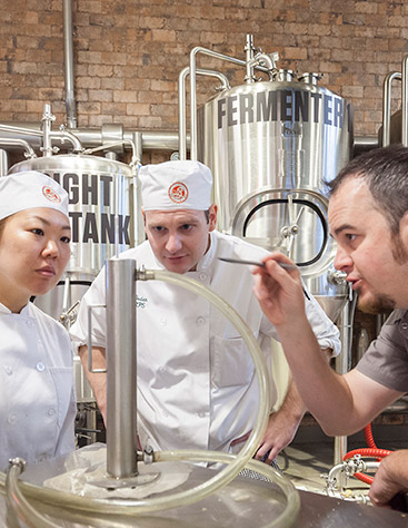Students of the Art & Science of Brewing course at the CIA examine beer brewing equipment.
