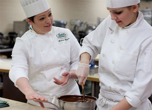 Baking and pastry arts associate degree students learn how to run a successful bakery café operation, prepare breads, plated desserts, chocolates, and confections. Here, instructor and student are preparing chocolate for one of the CIA fine-dining restaurants on campus.
