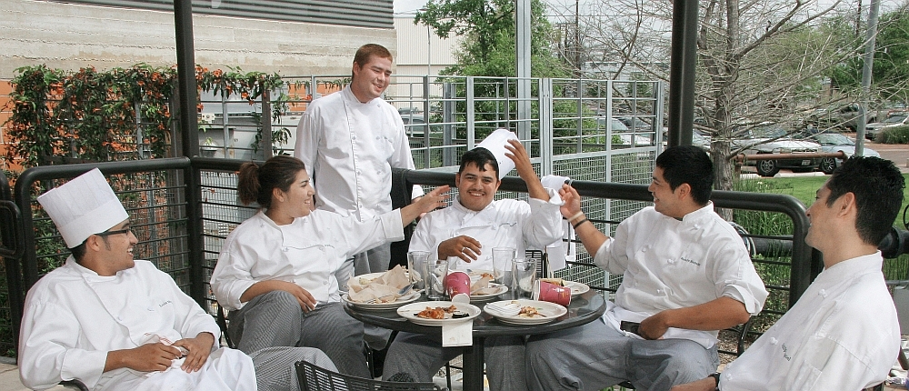 Students from The Culinary Institute of America in San Antonio, Texas enjoy a meal outside.