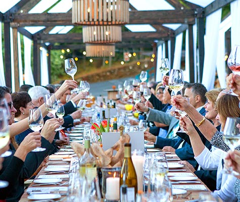 Long table with guests making a toast at one of the CIA's event venues for weddings, meetings and gatherings.